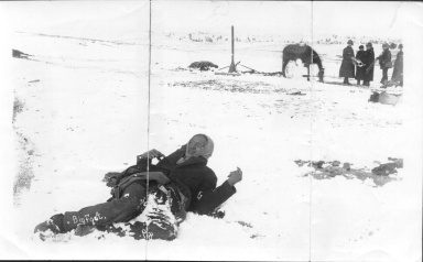 Chief Big Foot's frozen body on 3 January 1891. Major Whitside is pictured in the background, third from the left accompanied by Lieutenant Cloman and a surveying party. Source: Photograph donated by Ann S. Russell of Cornwall, New York.
