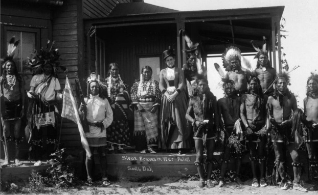 "According to the Denver Public Library likely taken in 1891 depicts Emma Sickels with Native American Sioux men and women on the porch of a Pine Ridge Agency building in South Dakota. The men wear breechcloths, roaches, headdresses, moccasins, legbands with bells and hold guns, rifle, bow and arrows, flags with stars and stripes and ""Harrison and Morton(?)."" The Sioux women wears dresses, leather belts with metal disks (conchos,) hair pipe earrings and necklaces. The white woman holds a parasol and wears a dress with a tightly fitted bodice and hat with a wide crown."
